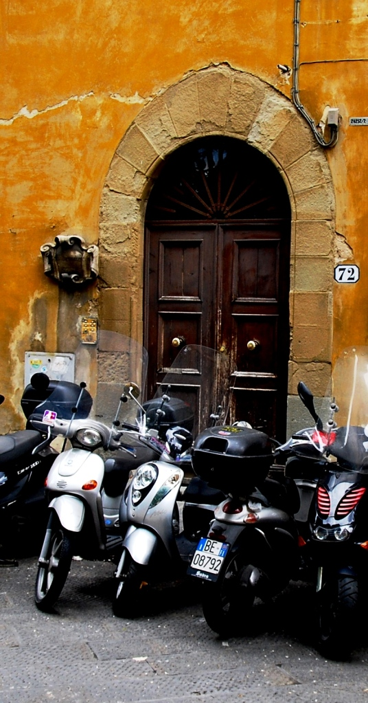 Firenze: motor bikes parked in front of an ancient door.
